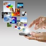 Handen rymmer pekskärmmobiltelefonen Arkivbilder