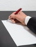 handen rymmer pennan som Arkivbilder