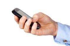 Handen rymmer smartphonen Arkivfoto