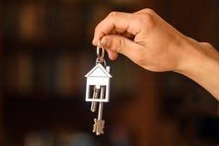 Handen rymmer tangenterna till lägenheten eller hemmet arkivbilder