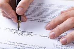 Handen sätter häftet i avtalet arkivbild