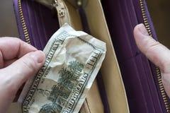 Handen sätter hundra dollarräkning i en plånbok royaltyfri bild