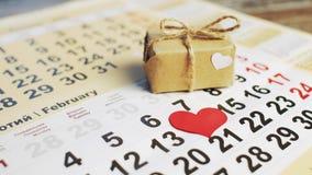 Handen sätter röd pappers- hjärta på numret 14 på en kalender och den lilla gåvan med en pilbåge Förälskelseferie arkivfilmer