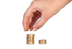 Handen satte mynt till bunten av mynt Royaltyfri Bild