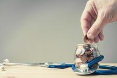 Handen satte myntet i en krus som sloggs in i en stetoskop royaltyfri fotografi
