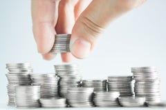 Handen satte pengarmynt till bunten av mynt, pengar som var finansiella, Busine Arkivbilder