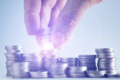 Handen satte pengarmynt till bunten av mynt, pengar som var finansiella, Busine Fotografering för Bildbyråer