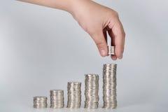Handen satte pengarmynt till bunten av mynt, pengar som var finansiella, Busine Arkivfoto