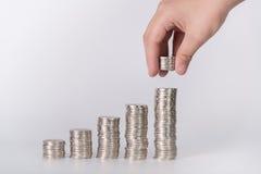 Handen satte pengarmynt till bunten av mynt, pengar som var finansiella, Busine Royaltyfri Fotografi