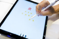 Handen skissar, genom att använda den Apple blyertspennan med nya Apple pro-Ipad Arkivbilder