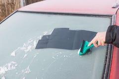 Handen skrapar is från vindrutan av bilen royaltyfria foton