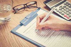 Handen skriver den personliga informationen på sjukförsäkringreklamationsformen Arkivbild