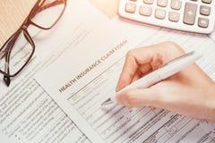 Handen skriver den personliga informationen på sjukförsäkringreklamationsformen Arkivbilder