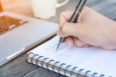 Handen skriver för att göra listan på anteckningsboken Arkivfoto