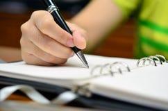 Handen skriver på en bok med en penna (selektiv fokus) - affärs- eller utbildningsanmärkningen Royaltyfri Fotografi