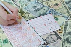 Handen skriver på lottsedel Arkivbild