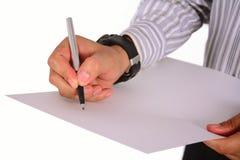 Handen skriver på vitboken som isoleras på vit Arkivfoto