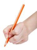 Handen skriver vid den isolerade orange blyertspennan Royaltyfria Bilder
