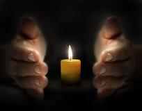 Handen skyddar stearinljuset Arkivfoto
