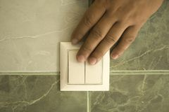Handen sl?cker ljuset i badrummet genom att anv?nda en v?ggstr?mbrytare fotografering för bildbyråer