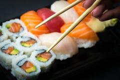 Handen som använder pinnar, väljer sushi- och Sashimirullar på en svart stenslatter Ny gjord sushiuppsättning med laxen, räkor, w Royaltyfri Bild