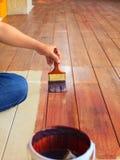 Handen som målar olje- färg på wood golvbruk för hem, dekorerade, H royaltyfri bild