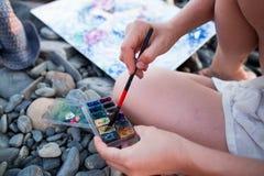 Handen som rymmer borsten med en palett av målarfärger Arkivbilder