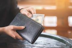 Handen som rymmer den 100 dollar banken, tar ut från plånboken Royaltyfria Bilder