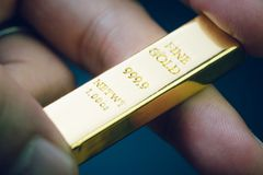 Handen som rymmer den guld- stången som investeringtillgång eller den säkra tillflyktsorten på finanskris, shinny tacka- eller gu royaltyfri foto