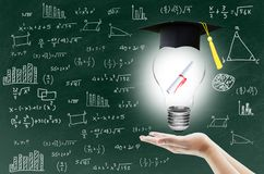 Handen som rymmer den ljusa kulan med attesteringen för avläggande av examen, visar påhittighetkunskapen Arkivbild