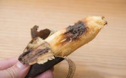 Handen som rymmer en övermogen banan med, avmaskar Fotografering för Bildbyråer