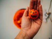 Handen som rymmer en chokladpumpa, formade orange arkivfoto