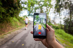Handen som rymmer en mobiltelefon som spelar Pokemon, går Royaltyfria Bilder