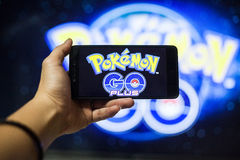 Handen som rymmer en mobiltelefon som spelar Pokemon, går leken med suddighetsbakgrund Royaltyfria Bilder