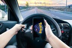 Handen som rymmer en mobiltelefon som spelar Pokemon, går modig vit körning royaltyfri fotografi