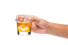 Handen som rymmer ett exponeringsglas av whisky på, vaggar Arkivfoto