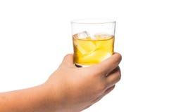Handen som rymmer ett exponeringsglas av whisky på, vaggar Fotografering för Bildbyråer