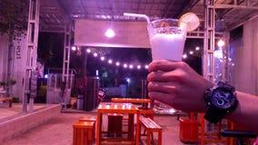 Handen som rymmer exponeringsglas av ny fruktsaft royaltyfri fotografi