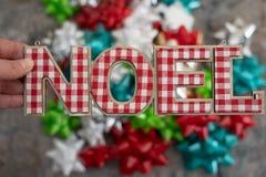 Handen som rymmer ordet Noel i plädbokstäver med denfokuserade gåvapacken, bugar i bakgrund Julferiebegrepp arkivbilder