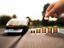 Handen som sätter pengarmynt, staplar att växa och kreditkorthårda slaget till och med terminalen på naturbakgrund arkivfoton