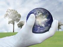 handen sparar världen Arkivbild