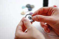 Handen syr en knapp med visaren och tråden closeup På a royaltyfri bild