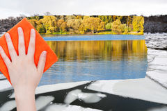 Handen tar bort isisflak i floden vid den orange torkduken Arkivfoto