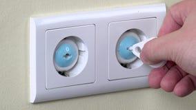Handen tar bort säkerhet pluggar i elektricitetsuttag på väggen stock video