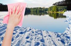 Handen tar bort snöfältet på den djupfrysta floden vid torkduken Arkivfoton
