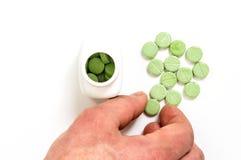 Handen tar de gröna preventivpillerarna Arkivbild