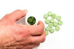 Handen tar de gröna preventivpillerarna Arkivbilder