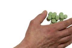 Handen tar de gröna preventivpillerarna Royaltyfri Bild