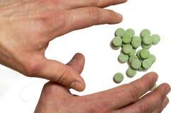 Handen tar de gröna preventivpillerarna Arkivfoton