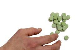 Handen tar de gröna preventivpillerarna Royaltyfria Bilder